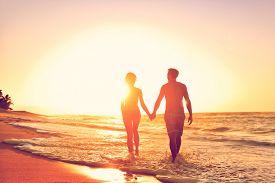 stock photo of beach holiday  - Honeymoon couple romantic in love at beach sunset - JPG