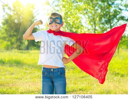 Superhero Kid Showing his Muscles over nature background. Little boy wearing superhero costume and h