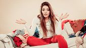 Worried Young Woman With Sofa Full Of Clothes. poster