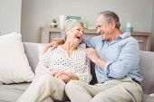 Romantic senior couple laughing while sitting on sofa at home poster