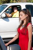 image of peeping-tom  - Young pretty woman in bright red dress unlocks her car door as a man watches stalking in the background from his pickup truck - JPG