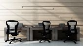Three chairs standing at empty workstation desks in office room. 3d Rendering. poster
