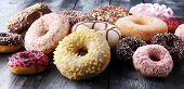 Assorted Donuts With Chocolate Frosted, Pink Glazed And Sprinkles Donuts. poster