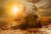 Man Riding Atv Through Mud Terrain Field poster