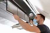 Male technician cleaning industrial air conditioner indoors poster