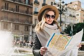 Young Smiling Woman Tourist In Hat And Sunglasses Stands On Street Of Ancient European City And Hold poster