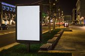 Vertical Blank Glowing Billboard On Night City Street. In Background Buildings And Road With Cars. M poster