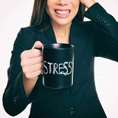 Stress - businessperson stressed at office. Business woman holding coffee cup with STRESS written. O poster