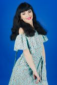 Brunette Smiles On Blue Background. Girl With Stylish Make Up And Bright Red Lips Wears Romantic Dre poster