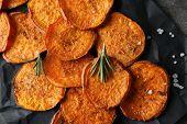 Tasty sweet potato chips on black parchment, closeup poster