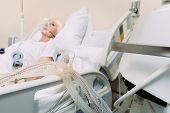 Постер, плакат: Modern Medicine Selective Focus On A Respiratory Support Of A Retired Lady Sleeping In The Backgrou