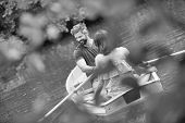 Black and white photo of  happy mid adult couple boating in lake during summer poster