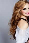smiling beautiful woman with long curly blond hair wearing bright pink lipstick and smoky eyeshadow
