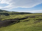 Two Hikers Backpack Travelers In Volcanic Landscape With Green Hills, Meadow And Lava Gravel Ground  poster