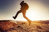 Hiker Man Jumps With Big Backpack To A Rock Against Mountains And Sunset Sun poster