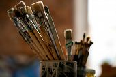 Set of paintbrushes for professional painting in tin can inside modern studio of drawing or classroo poster