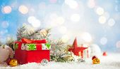 Christmas winter background with gift box, Christmas baubles and fir tree branches on snow. poster