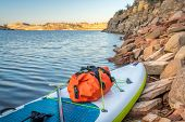 waterproof duffel on a deck of an inflatable stand up paddleboard, rocky shore of mountain lake - Ho poster