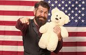 Looking For Fun Party Games. Party Man With Teddy Bear Pointing His Finger On American Flag Backgrou poster
