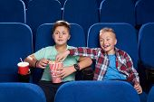 Front View Of Cunning Boy Stealing Popcorn While Male Friend Watching Interesting Film In Cinema. Ha poster