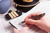 Close up of an airplane pilot hand filling in logbook with equipment including hat, epaulettes and o