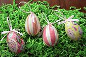 stock photo of decoupage  - Pretty decoupage egg decorations on shredded green easter grass - JPG