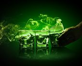 pic of absinthe  - Hand holding one of three glasses of green absinth with fume going out - JPG