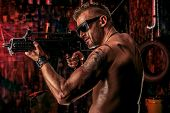 Portrait of a handsome muscular soldier man holding a machine gun. Grunge background.