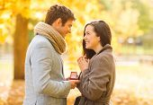 holidays, love, couple, relationship and dating concept - romantic man proposing to a woman in the a