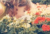 a small girl smelling some flowers vintage toned