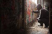 stock photo of spray can  - Illegal Young man Spraying black paint on a Graffiti wall - JPG