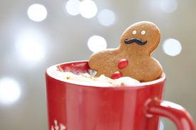 stock photo of gingerbread man  - Gingerbread cookie men in a hot cup of cappuccino - JPG