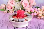 Composition with spa stones, candle  and flowers on color wooden table background