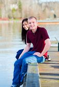 Beautiful Interracial Couple Sitting On Wooden Dock Over Lake