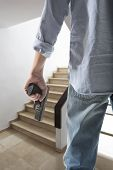 pic of outlaw  - Man holding gun against an stairs background - JPG