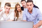 image of pissed off  - shocked and frustrated casual group of friends sitting on couch looking at laptop pissed off friends because results cheering on computer - JPG