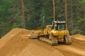 image of dozer  - Yellow excavator at work in winter forest - JPG