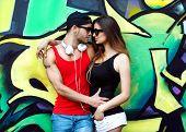 picture of graffiti  - fashion couple with sunglasses near the wall graffiti - JPG
