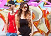 stock photo of graffiti  - fashion couple with sunglasses near the wall graffiti - JPG