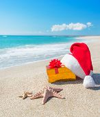 stock photo of santa claus hat  - Santa Claus hat and gold christmas gift box on the seashore with sea stars against blue sky - JPG