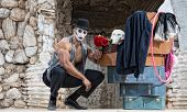 stock photo of clown rose  - Handsome muscular cirque performer kneeling next to luggage  - JPG