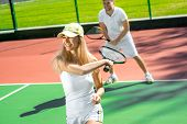 stock photo of married couple  - Young married couple playing tennis in white sportwear on the tennis court outside in the summer - JPG