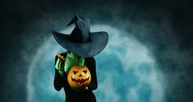 picture of horror  - Green witch opening Halloween carved pumpkin on full moon background - JPG