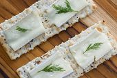 picture of brie cheese  - close up of slices of brie cheese on everything crackers with fresh dill - JPG