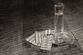 foto of paracetamol  - Tablets glass of water and scissors on a table i a glass plate in black white - JPG