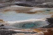 image of hot water  - A volcanic pool of hot aqua blue water and rust colored surroundings at Mammoth Hot Springs in Yellowstone National Park - JPG