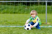 picture of little kids  - Funny happy little kid boy playing soccer and football and having fun outdoors on field - JPG