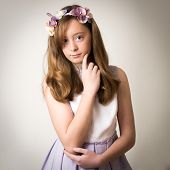 picture of tiara  - Studio portrait of a beautiful teenage ginger girl wearing a flower tiara and a pink outfit isolated against a grey background - JPG