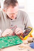 picture of multimeter  - Serviceman checks PCB with a digital multimeter in the service workshop - JPG