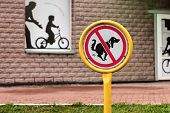 pic of dog poop  - round sign dog walking is prohibited on the background lawn and home - JPG